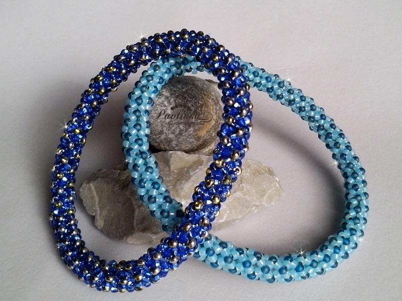 dva náramky z korálků položené na kamenech