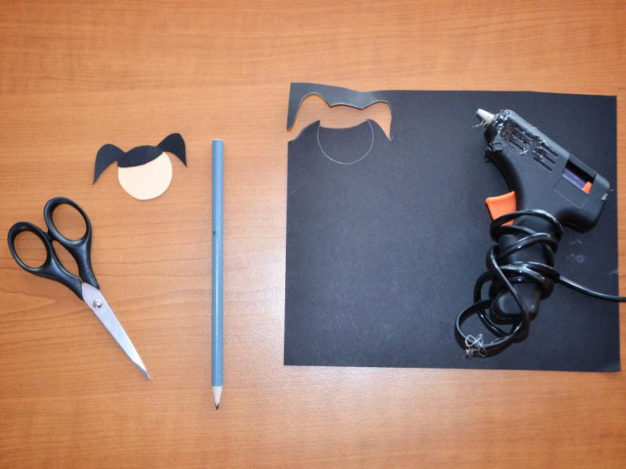 vystřižené vlásky přidělané tavnou pistolí ke kolečku z papíru