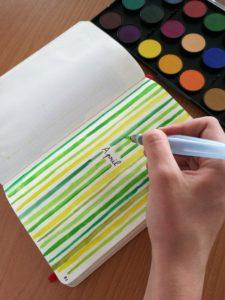 Zeleno žluté čáry v zápisníku vytvořené štetcem se zásobníkem na vodu